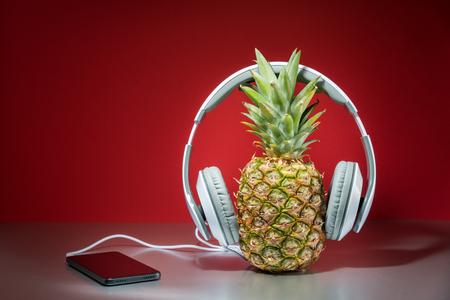 Music concept, pineapple with headphones, red background 스톡 콘텐츠