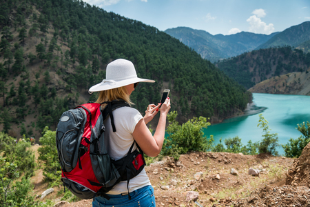 Woman backpacker using smart phone in mountains Standard-Bild
