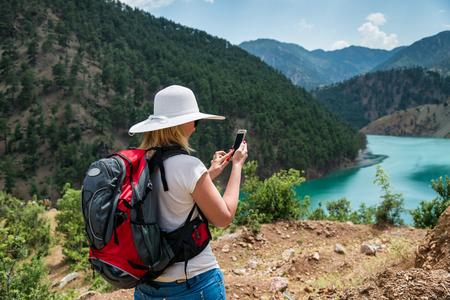 Frau Rucksacktourist mit Smartphone in den Bergen
