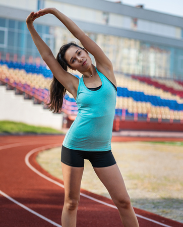 Young sporty woman doing fitness at stadium Imagens