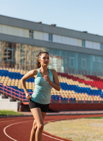 Young woman jogging in stadium in the morning