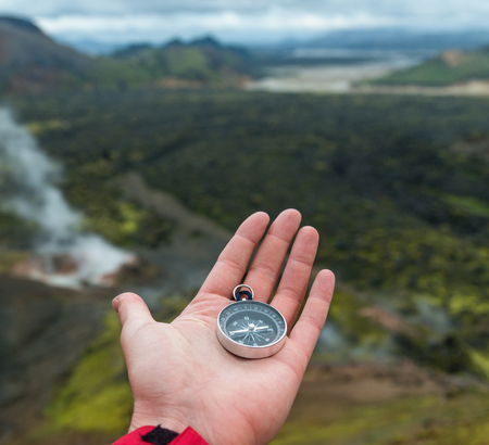 Traveler holding compass in Iceland mountains