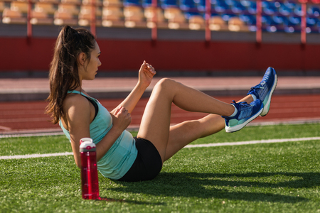 Young sporty woman doing abs exercise in stadium Imagens
