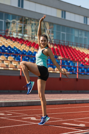 Asian sporty girl with jump rope in stadium