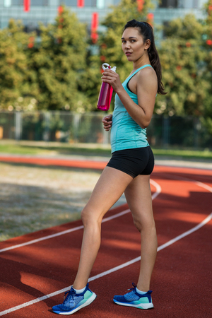 Young sporty woman with water flask in stadium