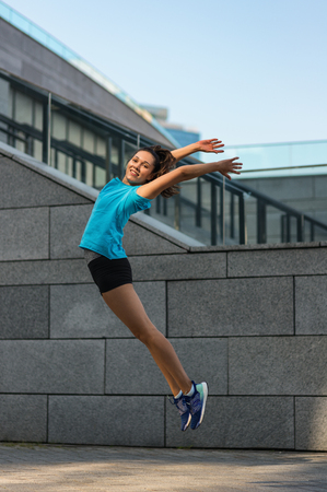 Active lifestyle, happy sporty young woman jumping outdoors
