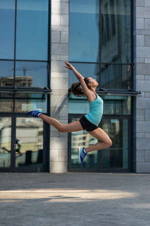 Young sporty woman jumping outdoors