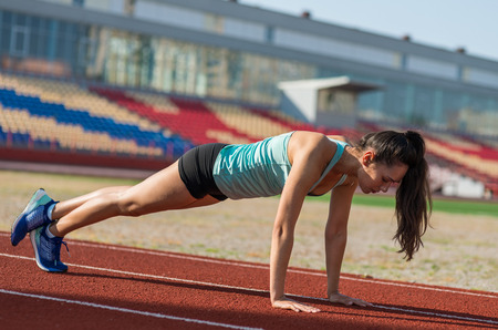 Sporty young woman training in stadium