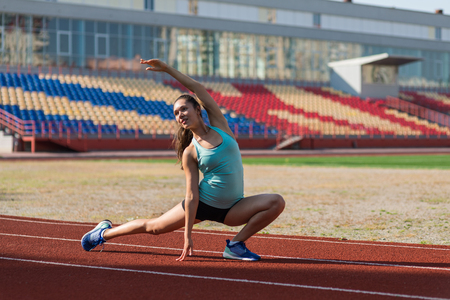 Young woman stretching at stadium in the morning Imagens