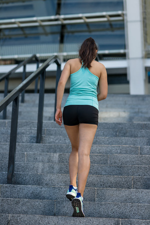Young sporty woman running up stairs Imagens