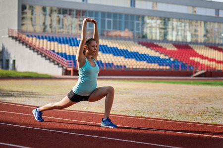 Young sporty woman exercising in stadium Imagens