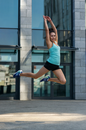 Sporty girl jumping in street