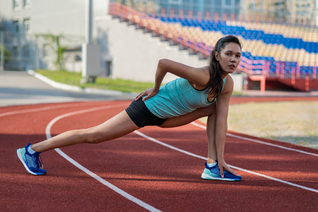 Young sporty woman stretching in stadium