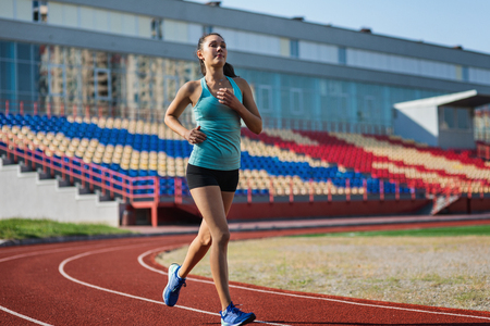 Young female jogging in stadium in the morning