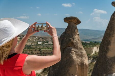 Woman traveling in Turkey, taking picture with smart phone