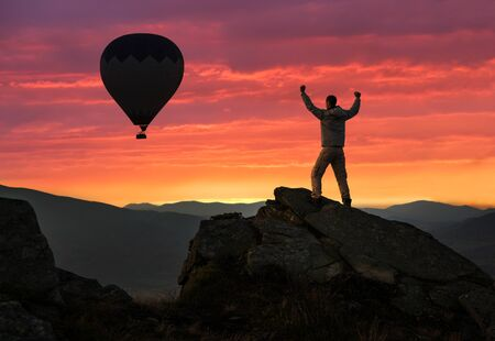 Hiker standing on mountain peak at sunrise, hot air balloon in sky