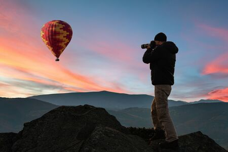 Man taking picture of beautiful sunset and hot air balloon in sky 写真素材
