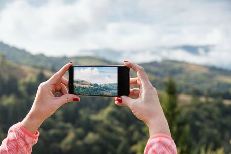 Woman taking picture in mountains using smart photne