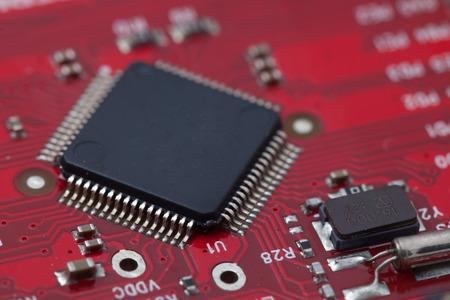 proto: Black IC on red PCB. Stock Photo