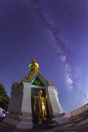Milky Way at Standing gold Buddha image name is Wat Sra Song Pee Nong in Phitsanulok, Thailand.