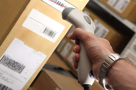 A man gets on the barcode scanner in operations directed on printed barcode. Warehouse scene.