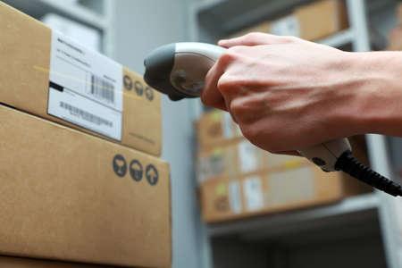 Ein Mann bekommt auf der Hüfte Scaner in Operationen, die auf gedruckten Barcode gerichtet. Warehouse Szene. Flachen DOF!