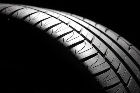 Modern high-performance sport summer tire close-up in a low key Studio shot