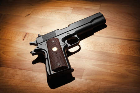 M1911 semi-automatic .45 caliber pistol on a wooden surface. Studio shot
