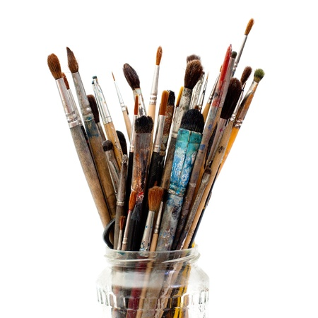 Assorted dirty painting brushes in glass flask Stock Photo