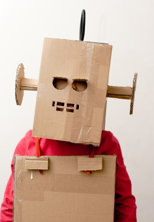 closed mouth: Robot Girl  Little girl with a cardboard box on his head  Stock Photo