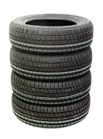 Four new tires stacked on one another on a white background Stock Photo