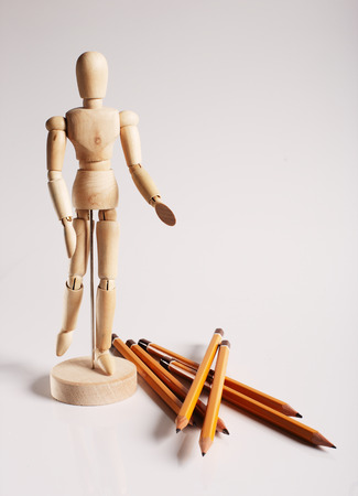 Wooden mannequin for painting with pencils on a white background