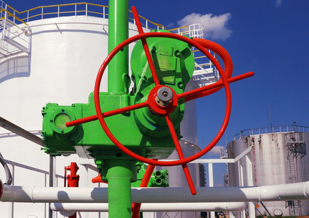 tanque de combustible: válvula grande verde sobre un fondo del tanque de almacenamiento de gasolina
