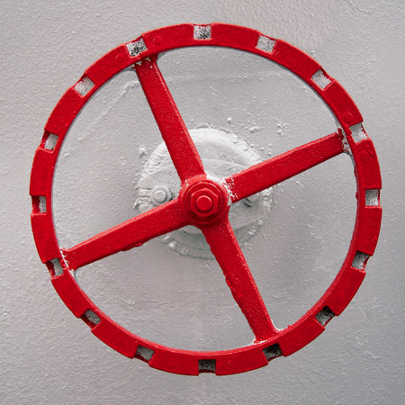 red hand: old red hand wheel on the wall of big oil tank