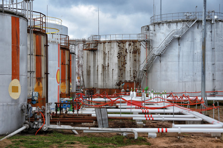 Large oil tank in industrial plant at twilight Stock Photo