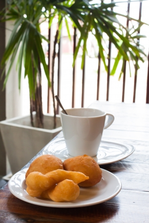 deep-fried doughstick with cofffe on table