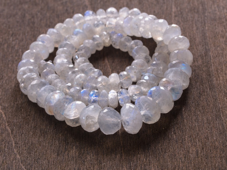 Jewelry from faceted mineral - moonstone on wooden background