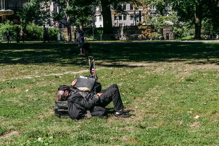 penury: New York, USA - September 20, 2015: Homeless man sleeps on the lawn in Central Park in Manhattan. Editorial