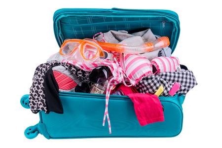 messy clothes: Messy suitcase full of clothes and accessories for vacation isolated on white background.