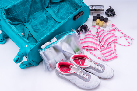 recommendations: Packing of suitcase to go on vacation isolated on white background. Recommendations for packing suitcases. Stock Photo