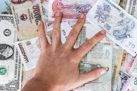 different countries: Greedy hand man presses the money from different countries Stock Photo