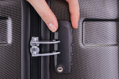 opens: Hand opens suitcase combination lock on the gray suitcase.