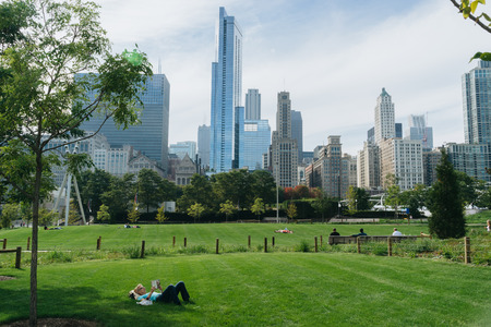 bp: Millennium Park, Chicago, USA - September 24, 2015: Woman is reading a book in Millenium park. Millenium Park is one of the parks major attractions.