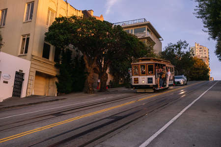 San Francisco, USA - September 30, 2015: Powell Hyde cable car, an iconic tourist attraction, descending a steep hill peak overlooking Alcatraz prison island and the bay.
