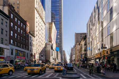 New York, USA - September 20, 2015:  People and yellow taxi on the street of New York.