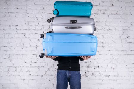 Man holding three heavy suitcases in hand. Travel light. 版權商用圖片 - 147461945