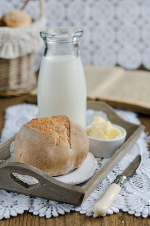 Fresh homemade bread rolls on a wooden tray with milk photo