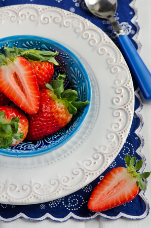 Fresh strawberries in a bowl on a bright blue background photo