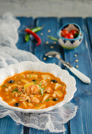 Fish soup with cod, potatoes, tomatoes and black olives photo