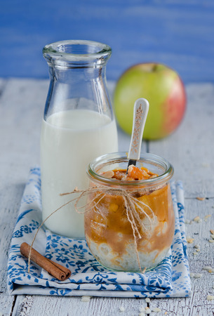Milk-rice dessert with caramelized apples in glass jar and milk bottle photo